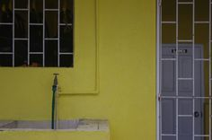 thisbe nissen, yellow wall, white gate, green hose, speightstown, barbados, 2013
