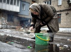woman scooping puddle water in Ukraine