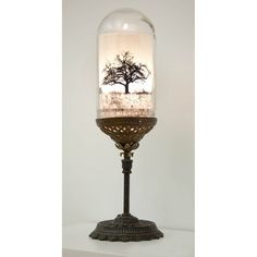 A photograph of a bare tree floats, illuminated inside a reclaimed glass dome as if preserved in oil. Electric Charroins take on the table top accent light brings a little steampunk to any room with its brass and copper fixture cobbled together from found parts. Finished with cloth-covered wire and antique style plug, its a light to behold.
