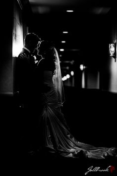 Bride and Groom getting romantic after their wedding ceremony. Shot in a hallway of a hotel. Intimate and very romantic