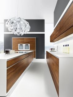 wood cabinetry + white waterfall counter-tops + statement light + black accent wall