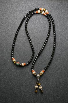 Materials: Black Obsidian beads (6mm), Bodhi seed beads, tiger eye beads, Nepal bead, antique sterling silver guru/spacers, high quality stretch cord Lengths: Total mala length: 32 in / 81cm When worn as a necklace, the guru bead is roughly 9.5 in / 24 cm below a collarbone