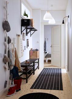 Ein kleiner Flur mit zwei Schuhbänken, einem Spiegel und TJUSIG Aufhänger in Weiß