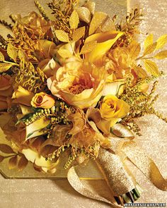 Glittering Bouquet The subtle shimmer in this golden bouquet of tree peonies, camel-colored roses, pieris buds, grevillea, and mini calla lilies comes in the form of metallic millinery finds and a ribbon-wrapped handle.