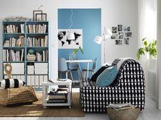 Saloncito con un sofá cama para dos personas con funda en blanco/negro, una mesa auxiliar blanca con ruedas, una mecedora moderna hecha con fibra de plátano y unas librerías de color turquesa claro.