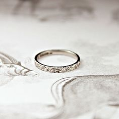 2mm width, platinum, floral engraved ring.{shown here in UK size J}This ring is flat court shape, meaning it is flat on the outside and slightly curved on the inside for a comfortable fit.All our engraving is done entirely by hand, using methods unchanged in hundreds of years.This pattern has been achieved using tiny sharp chisels, by our very experienced engraver here in London.Each one is engraved separately, giving each ring it's own unique hand finish. hall...
