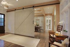 The barn door, which lends character and charm to this entry feature, was actually a new door that Leslie from Segreto Finishes refinished to look aged. The door also serves as a divider between the kitchen and more formal social areas when the couple entertains. All the beams were stained in a pine aged finish.