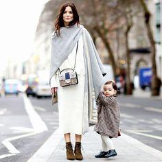 Hedvig Opshaug e seu filho, ela veste um maxi dress branco com botas.