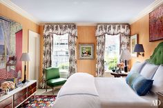 The master bedroom curtains combine a Tulu print with a Samuel & Sons fringe; a Kravet satin covers the vintage slipper chair, and the headboard was custom made by Luther Quintana with a Lee Jofa velvet.