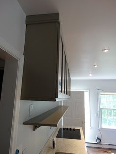 The upper cabinets were mounted a bit higher than standard ones - 22-inches above the countertop versus 18-inches. We then installed a shelf with corbels underneath them for frequently used items.