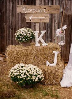 déco mariage avec balles de paille et chrysanthèmes blanches, enseigne en bois, bougeoir bocal