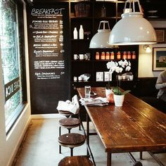 white pendants + wood tabe and stools and chalkboard wall