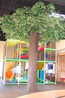 Worlds of Wow - a fun tree conceals a structural support beam in front of this indoor soft-contained play attraction at Trinity Lutheran Church in Lisle, IL.