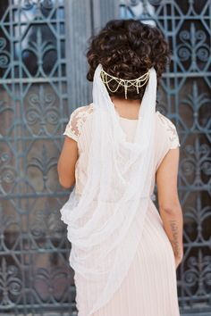 Gossamer Tulle Drape Veil - Style #321 Rich with texture this gossamer tulle veil has a luxurious crushed tulle finish. Created using the most soft and sheer textiles which allows for this design to drape gently from two combs, creating a swag effect. This unique silhouette is perfect for the modern discerning bride looking for an understated yet beautiful veil. Gauzy and wispy this lightweight veil floats from your hair. Left simple so that you may adorn this veil as you choose. Wear it…