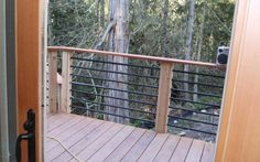 This deck railing has a wooden top with horizontal metal rails.