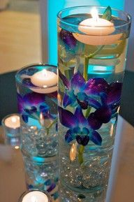 Candles floating in clear vases with submerged flowers...but using assorted plum and peacock glass river rocks in the bottom! And multiple sizes for the vases, and some small ones have a single or double floating flower. cute centerpiece