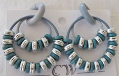Here are double blue rubber rings with blue silver tone spacer type beads . They hang on rubber clips and are non-pierced. They are very comfortable and cannot hurt your ears. They simply clip on your ear lobe.