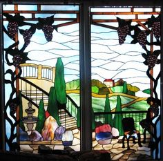 Custom stained glass window panels for lake home at Lake of the Ozarks featuring grape vines and patio overlooking Italian Tuscany scenery. The client reads, so we incorporated a small table complete with her current book and a glass of wine.  By Les & Sandy Burnett of GlassMoose.com