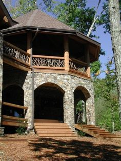 A stone turret acts as a two story attached gazebo. Featuring twig railing. | Handcrafted Chink Style Log Home | Caribou Creek Log and Timber on Caribou Creek Log  Timber  http://cariboucreekloghomes.com/social-gallery/a-stone-turret-acts-as-a-two-story-attached-gazebo-featuring-twig-railing-handcrafted-chink-style-log-home-caribou-creek-log-and-timber