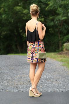 Island-Inspired: faux sock bun, black cami crop top, bright printed graphic skirt, island wear, beach style, gold wedge sandals, gold Brahmin Amelia crossbody bag
