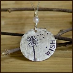 """By """"Tag... You're it""""... A hammered, distressed 1 inch sterling silver tag with a hand stamped dandelion blowing in the wind.  A freshwater pearl hangs above it."""