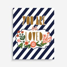"""With an effortless modern style, Lucy Darling offers a high-quality """"You Are So Loved"""" navy striped, floral art print designed to help celebrate the darling mom"""
