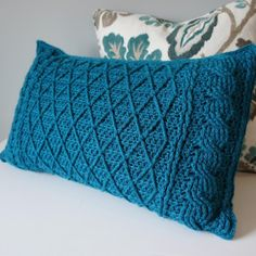 Add a splash of color and sophistication to your favorite space by creating this pillow cover. The cables and lattice work provide tons of texture and interest and is sure to work with any decor - download the pattern from LoveKnitting!