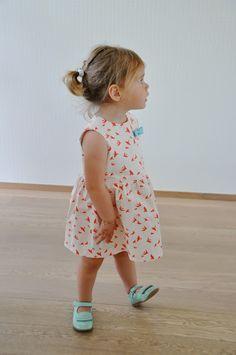 Une robe d'été pour les bébés proposée par Emma et Mona . Le patron est disponible de la taille 62 à 92; Ce modèle est disponible en trois finitions, avec volants simples ou plissés sur les manches ou sans. Une version tout en jersey est aussi détaillée....