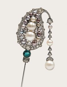 Natural pearl, emerald and diamond jabot pin, Cartier, 1920s. Of Indian inspiration, set with natural pearls of various colours, a circular-cut emerald, cushion-shaped, circular-cut and rose diamonds, suspending a line of diamonds and natural pearls; the keeper set with circular-cut diamonds, calibré-cut emeralds and a natural pearl.
