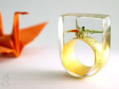 While at first glance they may appear like ordinary jewelry, take a closer look and you'll find uniquely designed resin rings that contain an entire world all their own.