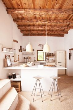 Open rustic kitchen with exposed beams, wicket pendant lights and industrial silver stools