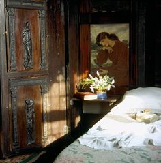 A corner of the Oak Room at Wightwick Manor with period carvings and paintings based on early Rossetti works.