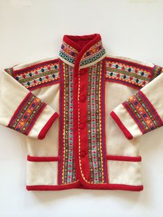Chlidrens Saami Scandinavian Lapland Jacket w Decorative Folk Trim.  Enchanting.  Cream color wool with hems rimmed in cherry red.  Extensive colorful nordic folk trim.  Four fabric covered buttons serve as closure w an additional sewn inside.  Lapland Style - Northern Norway Sweden, Finland in the Sammi or Sami Style.  I would guess this coat could fit a child fro ages 3-7. Coat can be worn loose, tight.  Please refer to measurements!!!!  Samii Coat / 100% wool / M  Trim most likel...