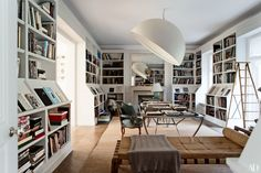 A colossal Paul Cocksedge enameled-aluminum light hangs over the library's Joris Laarman table. Louis XV beechwood chairs upholstered in blue calfskin; Pierre Jeanneret teak daybed; antique bamboo library ladder.