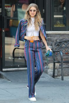 Gigi Hadid looking cool in New York wearing a striped suit and crop top with sunglasses.