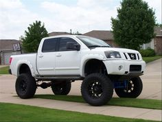 Nissan Titan with lift kit, running boards and fender flares.