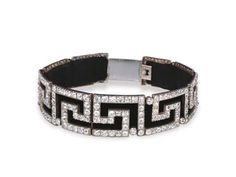 AN ANTIQUE DIAMOND CHOKER   The nine graduated panels of cushion-shaped diamond Greek Key design to the later black velvet band and clasp, mounted in silver and gold, circa 1880, 31.5 cm. long