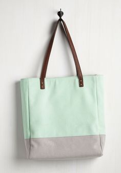 While the daily necessities you need to haul may change, the chicness of this mint tote in which you carry 'em is unwavering! Eternally cool with its chocolate brown, vegan faux-leather straps, gold hardware, and grey colorblocked bottom, this tote boasts stylish reliability for the ages.