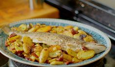 Nadiya Hussain served up whole baked sea trout with potatoes, lemon and sundried tomatoes on Nadiya's British Food Adventure. The ingredients are: 750g new potatoes, 1 small unwaxed lemon, sliced, 1 tbsp black onion seeds, 1 x 280g jar sundried tomatoes in oil, ¼ tsp caster sugar, 2 whole fish (about 400g) such as sea bass, sea trout or Dover sole, cleaned, small bunch fresh parsley, small bunch lemon thyme, sea salt and freshly ground black pepper. The recipe is available in Nadiya's new…