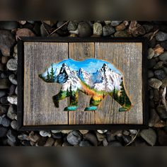 """This is a part of my smaller collection. This piece is made out of  reclaimed woof with a cut out grizzly bear. Inside is painted a beautiful  lake and mountain scene with acrylic paint. Measures at 10""""x14""""."""