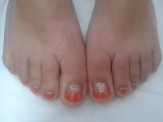 A dry pedicure complete with CND Shellac 'Electric Orange' nail polish and 'Silver Holographic' glitter fade on all toes.