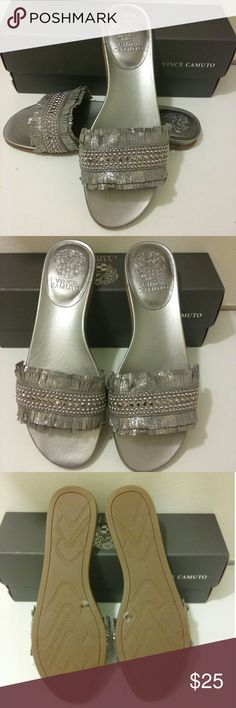 Vince Camuto Ettina Grey Sandal The Ettina is flat slip-on sandal flaunting a foiled vamp strap with fringed ends and a sprinkling of rockstar-worthy studs.  Style these shoes with a breezy midi skirt or cropped jeans. Metal Grey Metal Dust Suede or leather upper, man-made lining and sole. Vince Camuto Shoes Sandals