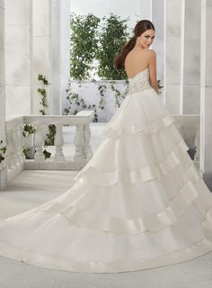 An intricately beaded strapless bodice on a flounced organza ball gown with wide satin trim