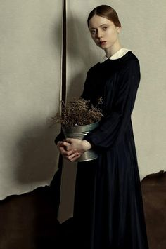 'Woman with flowers' by Romina Ressia, 2015 - a photograph that looks like a painting, of a woman who might have stepped out of a Hammershøi interior (via James Russell)