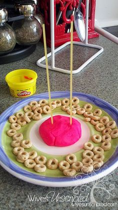 Fine motor - working on hand strength when shaping the play dough, and precision and coordination when placing each cheerio on the straws.