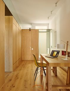 Built Architecture uses oak cabinetry to reorganise a mosaic-floored Barcelona apartment