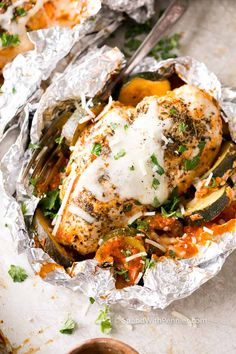 Parmesan Chicken Foil Packets are a complete dinner in a tidy little packet! Veggies, tomato sauce & chicken breasts are topped with mozzarella cheese.