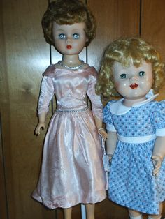 My 2 new dolls from the Doll Show.  One is a grocery store doll in fancy clothes & jewelry.  The other is an unmarked Saucy Walker? type doll.  The lady made her dress.  She has teeth, jointed legs & is a walker.  I love her.