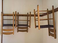 Shaker chairs hung on pegs.