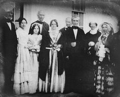 PRESIDENT JAMES POLK and his family, with future president JAMES BUCHANAN (far left) together on the South Portico at the White House. The woman to President Polk's left (head blurred) is former FIRST LADY DOLLEY MADISON. -- 1849